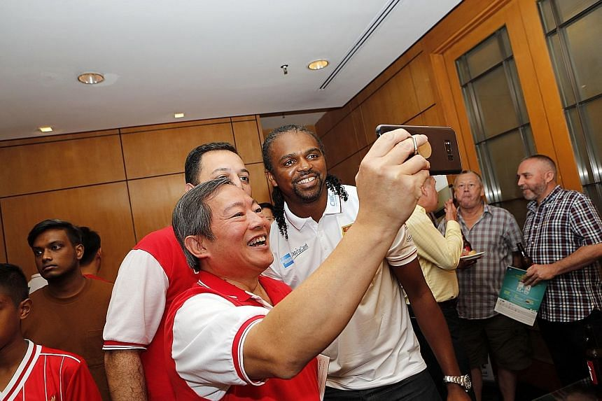 Liverpool Masters winger Steve McManaman (left) exchanges pre-match niceties with his Arsenal counterpart and Masters debutant Robert Pires. Left: Fans get a selfie with ex-Arsenal forward Nwankwo Kanu. The Gunners are keen to avenge their loss in In