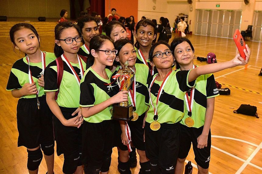 Above: Nursulizati Suhairat takes a wefie with her team-mates from Farrer Park Primary School. The Primary 4 pupil and her team emerged victorious in the junior girls category in this year's SPH Foundation National Primary Schools Tchoukball Champion