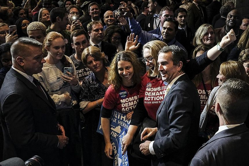 Mr Ralph Northam, the Democratic candidate for governor in Virginia, greeting supporters after his election victory, in Fairfax, Virginia, on Tuesday. Mr Northam registered a commanding victory, overcoming a racially charged campaign by his Republica