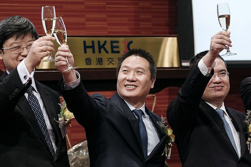 (From left) China Literature president Shang Xuesong and co-CEOs Liang Xiaodong and Wu Wenhui, at the company's listing ceremony at the Hong Kong stock exchange. Demand for the IPO was such that retail investors bid for 625 times the shares on offer.