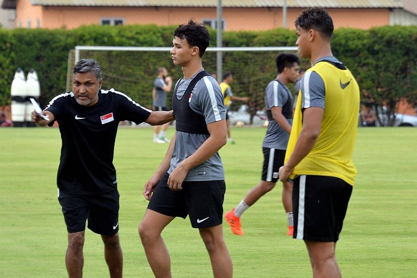 Singapore head coach V. Sundram Moorthy (left) giving instructions to Ikhsan Fandi and Irfan Fandi (right) during a session of team training at the Geylang Field.