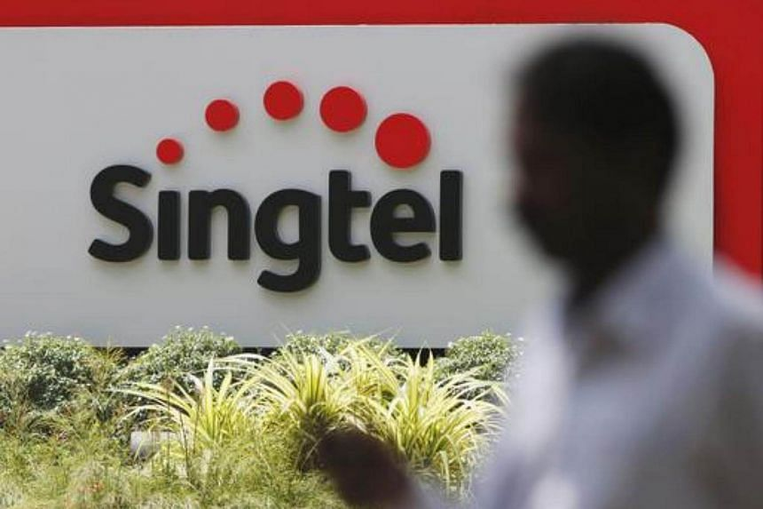 A man using his mobile phone passes a Singtel signage at their head office in Singapore.