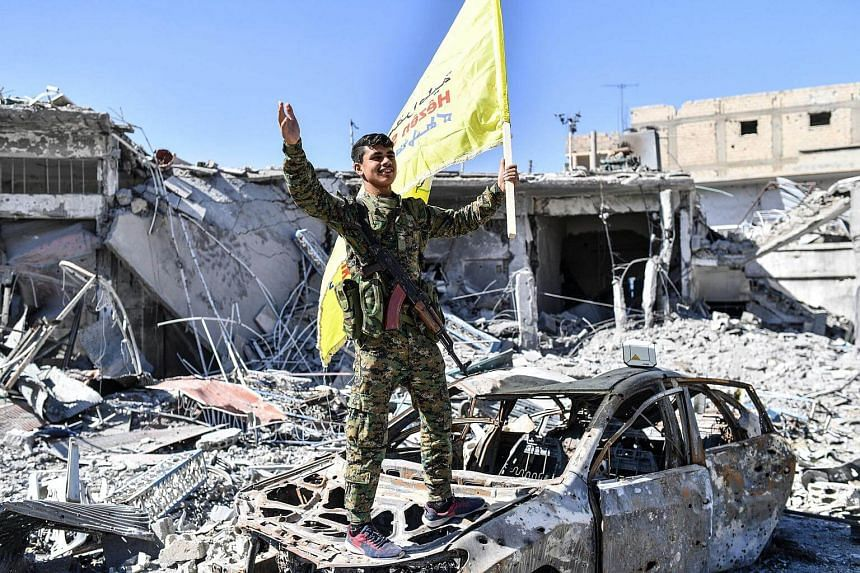 A member of the Syrian Democratic Forces (SDF), backed by US special forces, holds up their flag at the iconic Al-Naim square in Raqa.