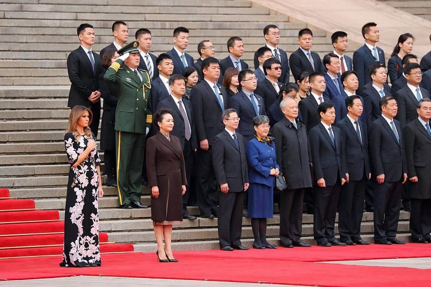 US first lady Melania Trump and China's First Lady Peng Liyuan watch as US President Donald Trump takes part in a welcoming ceremony with China's President Xi Jinping in Beijing.