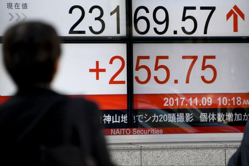A pedestrian walks past an electronics stock indicator at the window of a security company in Tokyo displaying the current rate of Tokyo Stock Exchange on Nov 9, 2017.