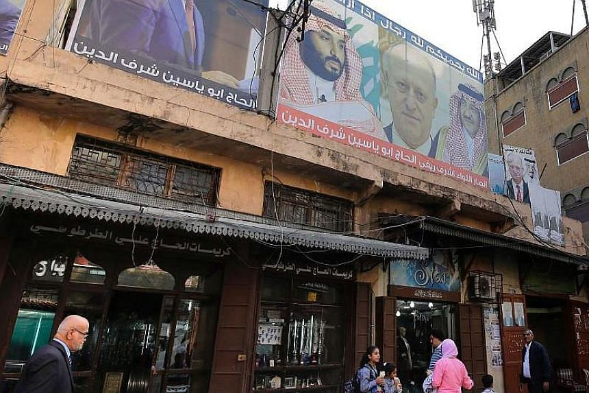 Lebanese pedestrians walk past shops decorated with posters bearing pictures of Saudi Arabia's Crown Prince Mohammed bin Salman (left), his predecessor, ousted crown prince Mohammed bin Nayef (third right), and King Salman bin Abdul Aziz (right), in