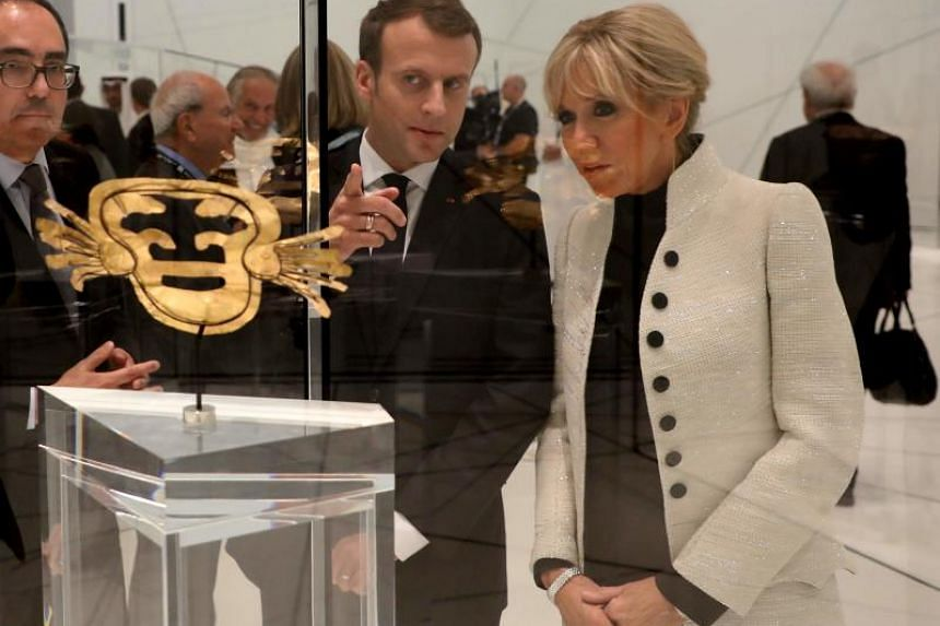 French President Emmanuel Macron and his wife Brigitte Macron look at a piece of art as they visit the Louvre Abu Dhabi Museum on Nov 8, 2017 during its inauguration on Saadiyat island in the Emirati capital.