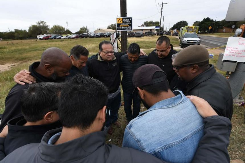 A group of 12 pastors from local churches pray beside a memorial service for victims of the mass shooting that killed 26 people in Sutherland Springs, Texas on Nov 8, 2017.