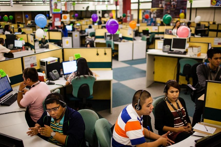 Employees take phone calls as they work in an SPi Global call centre in Manila.