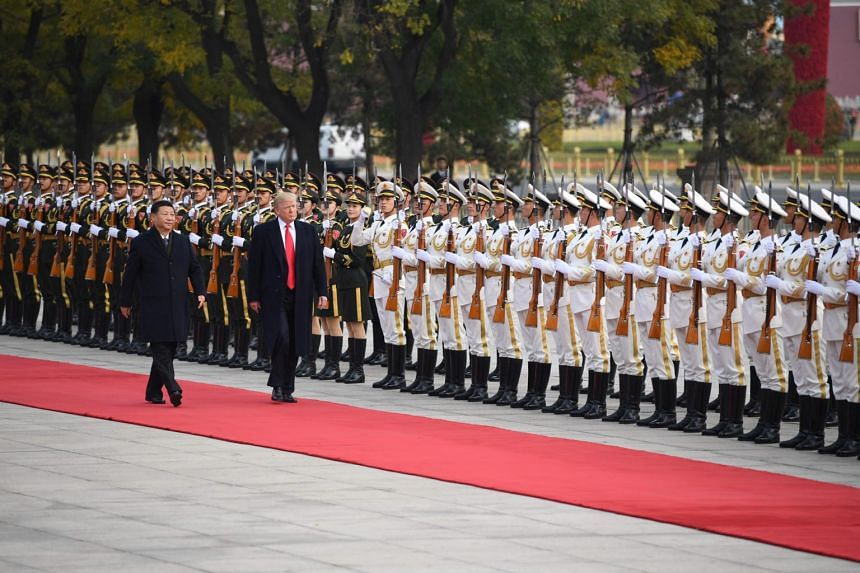 China's President Xi Jinping (left) and US President Donald Trump review Chinese honour guards during a welcome ceremony at the Great Hall of the People in Beijing on Nov 9, 2017.