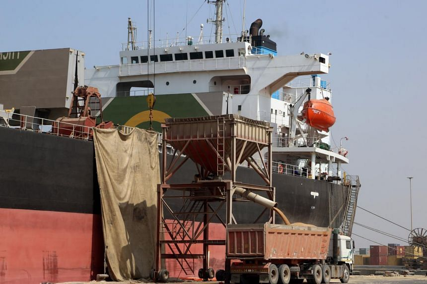 A crane unloads wheat from a cargo ship in Yemen's rebel-held Red Sea port of Hodeida on Nov 7, 2017.