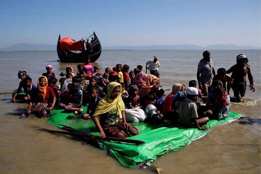 Rohingya refugees sit on a makeshift boat as they wait permission from Border Guard Bangladesh to continue after crossing the Bangladesh-Myanmar border at Shah Porir Dwip near Cox's Bazar, Bangladesh on Nov 9, 2017.