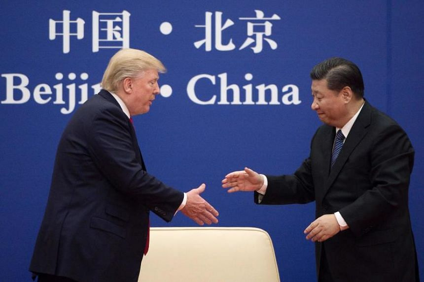 """China's President Xi Jinping shakes hands with US President Donald Trump (L) during a business leaders event at the Great Hall of the People in Beijing on November 9, 2017. Donald Trump urged Chinese leader Xi Jinping to work """"hard"""" and act fast to"""
