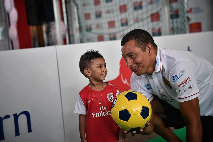 Two-year-old Arthur Zachary with former Arsenal and Brazil player Gilberto Silva at the Score For Charity event yesterday.
