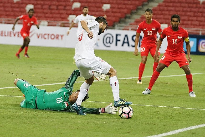 Singapore goalkeeper Hassan Sunny saves at the feet of Lebanon midfielder Mohamad Haidar during the 1-0 defeat yesterday. The custodian's stellar performance was a highlight of the match.