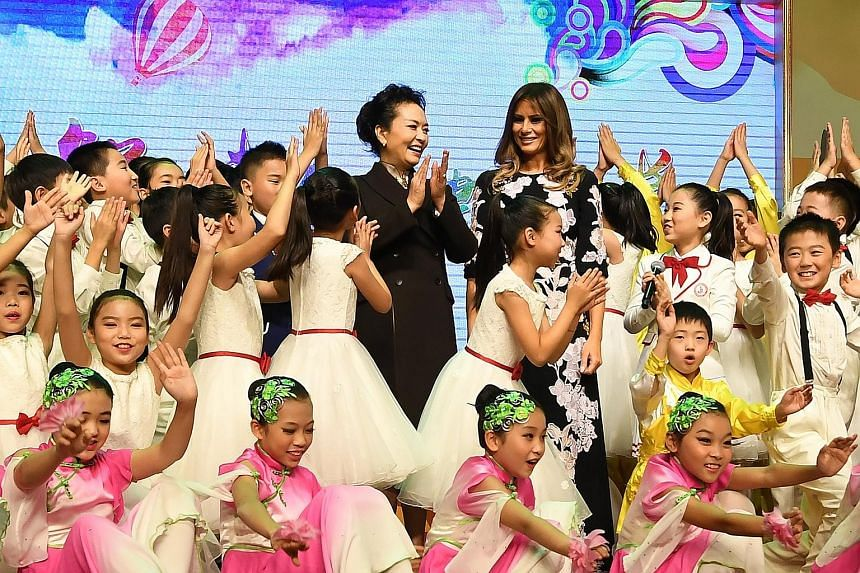 US First Lady Melania Trump and China's First Lady Peng Liyuan surrounded by pupils after a cultural performance during their visit to Banchang Elementary School in Beijing yesterday.