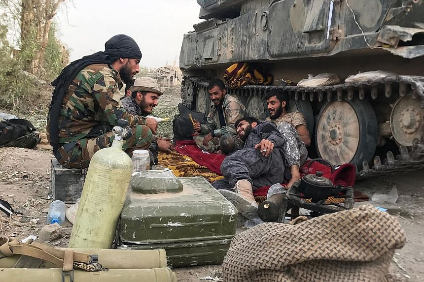 Syrian government forces resting beside an armoured vehicle in Deir Ezzor, sited on the western bank of the Euphrates River, on Sunday, after retaking the city from ISIS militants.