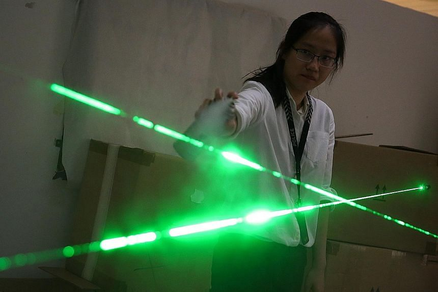 Above: Team officer-in-charge Lim Li Shi using a spray to trace laser beams that outline the trajectory of bullets. Left: A forensic light source being used to detect traces of evidence such as fingerprints.
