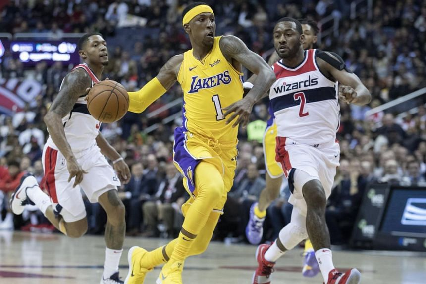 Los Angeles Lakers guard Kentavious Caldwell-Pope (centre) dribbles between Washington Wizards guard John Wall (front, right) and Washington Wizards guard Bradley Beal (front, left) during the first half of the NBA game between the Los Angeles Lakers