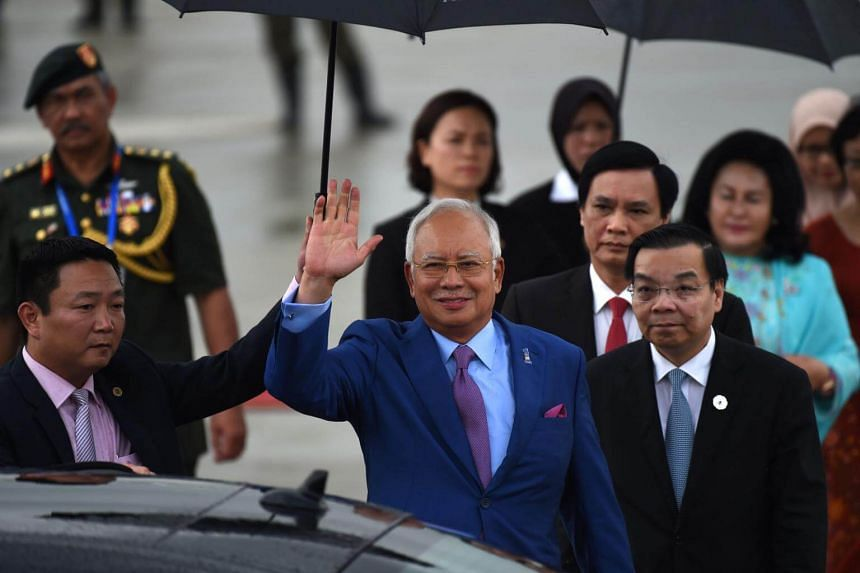 Malaysia's Prime Minister Najib Razak (centre) waves upon his arrival at the international airport ahead of the Asia-Pacific Economic Cooperation (Apec) Summit in the central Vietnamese city of Danang.