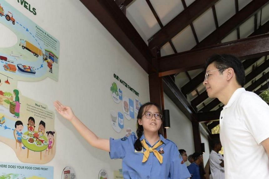 A Girl Guide sharing the concept of food miles with National Development Minister Lawrence Wong at the Farm Zone in the new Jacob Ballas Children's Garden extension.