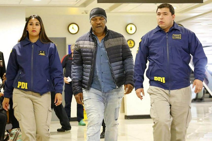 US boxer MikeTyson (centre) accompanied by two agents of the PDI at the international airport of Santiago, Chile.