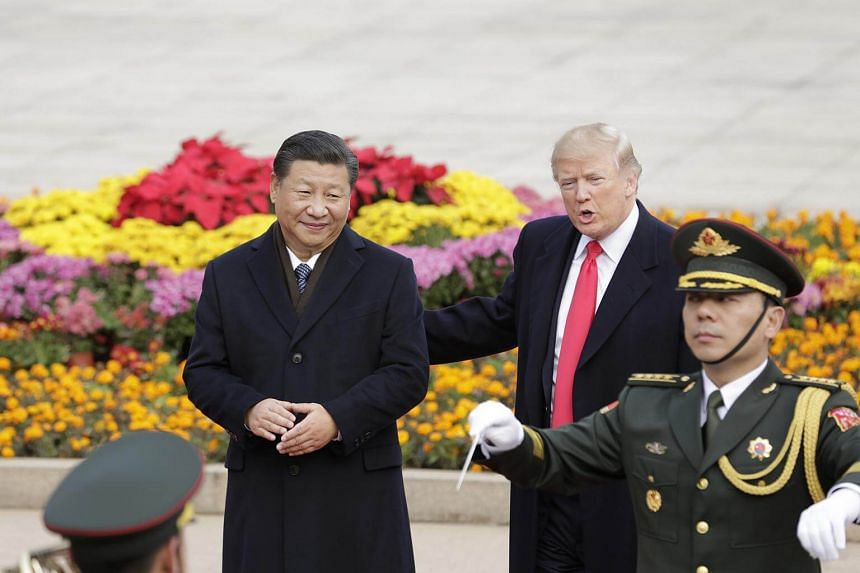 US President Donald Trump (centre) speaks as he stands next to China's president Xi Jinping in front of members of the Chinese People's Liberation Army (PLA) band during a welcome ceremony outside the Great Hall of the People in Beijing.