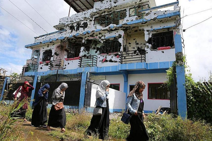 Residents who returned from evacuation centers walk past a bullet-ridden house believed to have been rented by pro-Islamic State militant group leaders Isnilon Hapilon and Omar Maute before their attack on the region, in Marawi city, Philippines on O