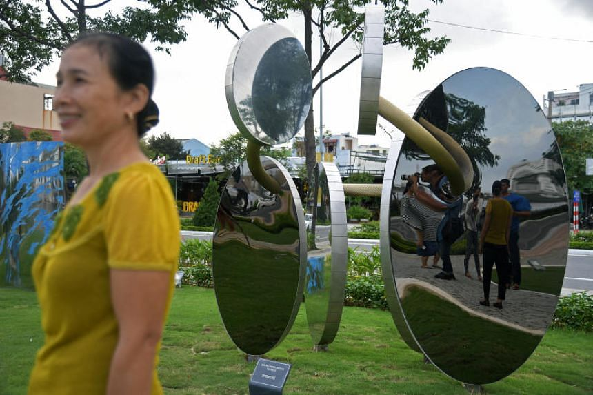 Locals in Da Nang take pictures in front of the sculpture by Singaporean artist Tan Wee Lit, which now adorns a park in Da Nang, Vietnam.