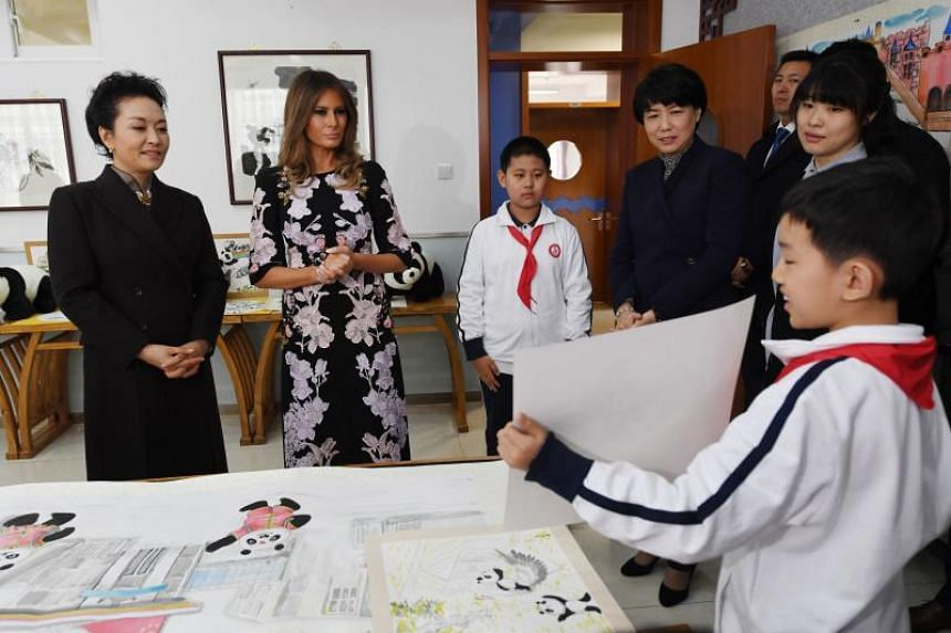 US First Lady Melania Trump (2nd left) and China's First Lady Peng Liyuan (left) are shown an artwork in a calligraphy class during a visit to Banchang Primary School in Beijing on Nov 9, 2017.
