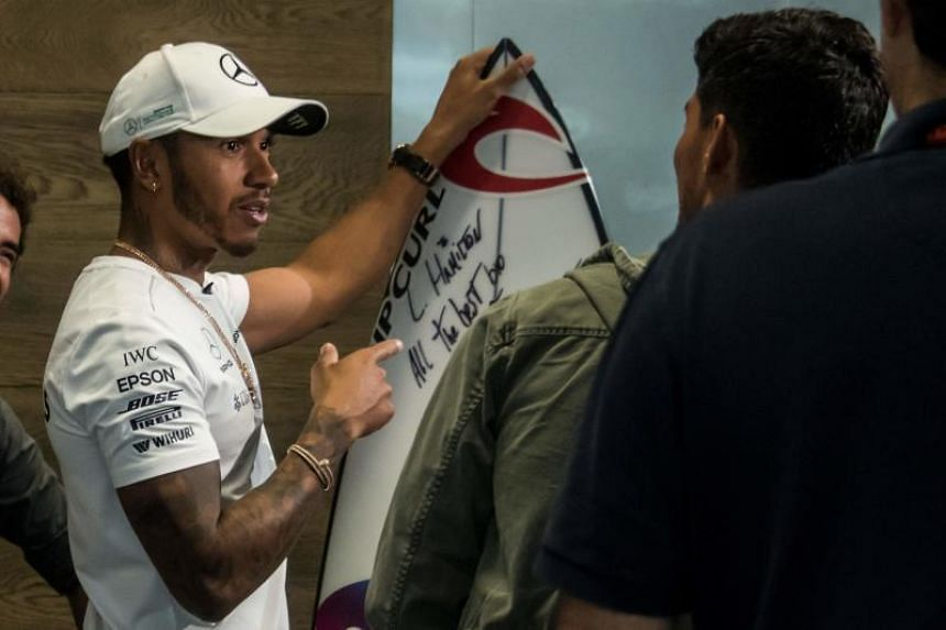 Mercedes' British driver Lewis Hamilton receives a surfboard from Brazil's surfer Gabriel Medina (right) at the Interlagos pits on Nov 9, 2017, in Sao Paulo, Brazil.