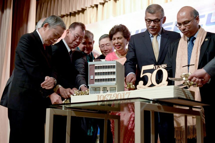 Chief Justice Sundaresh Menon (second from right) and president of the Law Society of Singapore Gregory Vijayendran (far right) cut a cake with other past presidents of the Society.