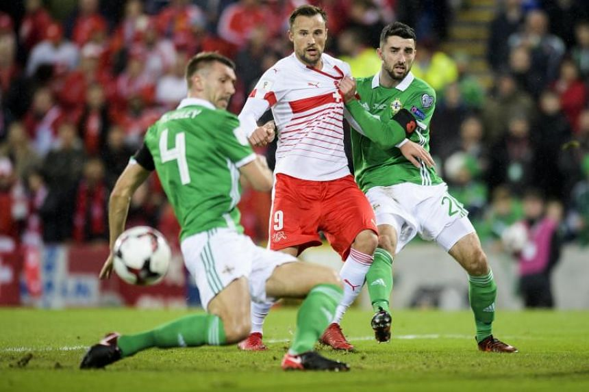 Switzerland's Haris Seferovic (centre), fights for the ball with Northern Ireland's Gareth McAuley (left), and Conor McLaughlin.