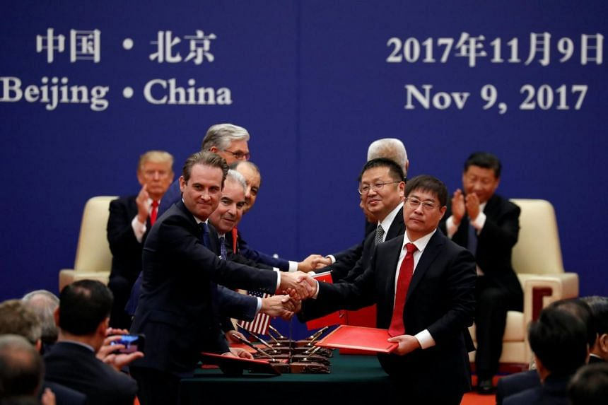Business leaders shake hands as US President Donald Trump and China's President Xi Jinping attend their signing ceremony at the Great Hall of the People in Beijing, on Nov 9, 2017.