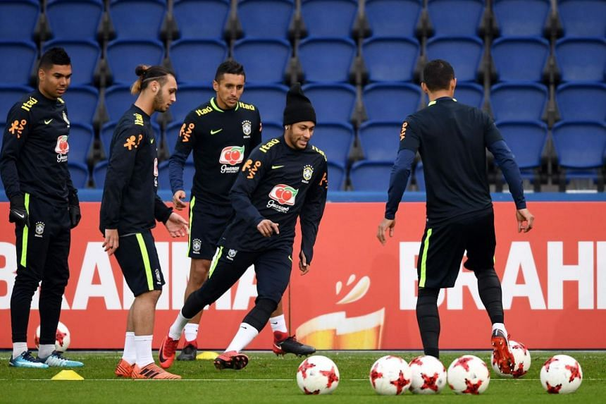 Neymar (centre) eyes the ball in front of defender Marquinhos during a training session at the Parc des Princes stadium in Paris on Nov 8, 2017 as part of the team's preparation for the friendly football match against Japan.