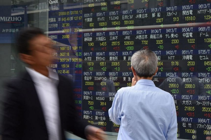A pedestrian looks at an electronics stocks indicator displaying numbers of the Tokyo Stock Exchange in Japan.