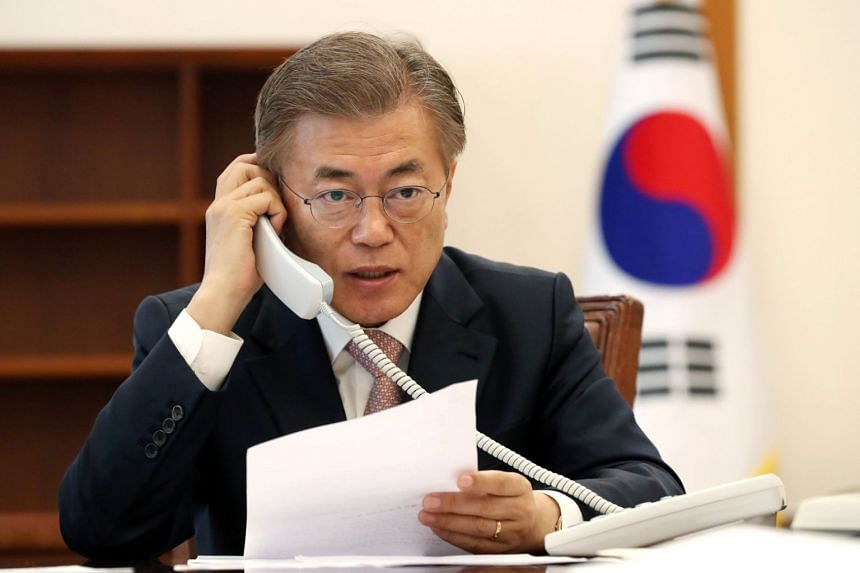 South Korean President Moon Jae In speaks with Chinese President Xi Jinping on the telephone at the presidential Blue House on May 11, 2017.