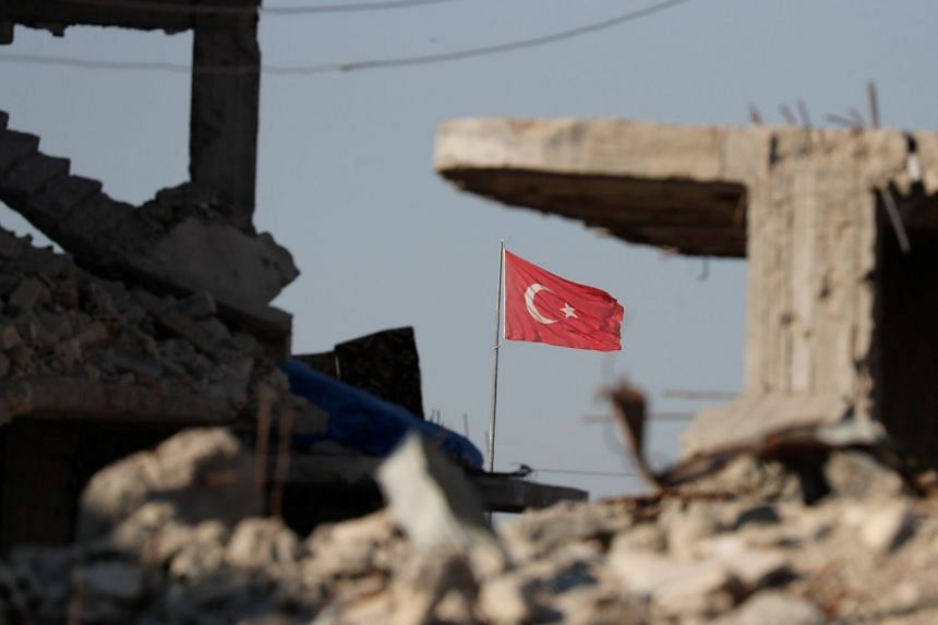 A Turkish flag at Turkey's border gate, overlooking the ruins of buildings destroyed during fightings with Isis militants in Kobani, Syria on Oct 11, 2017.