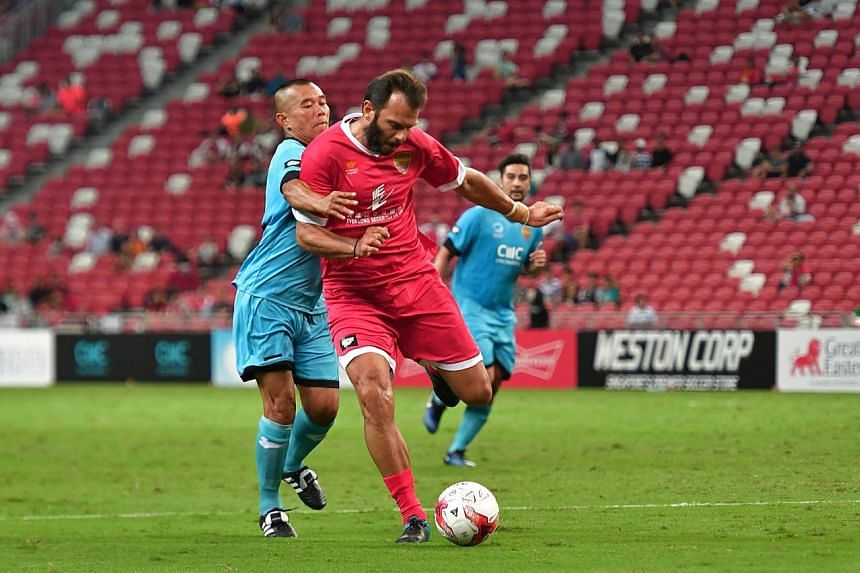 Singapore's Steven Tan square off with Liverpool masters' Patrik Berger.