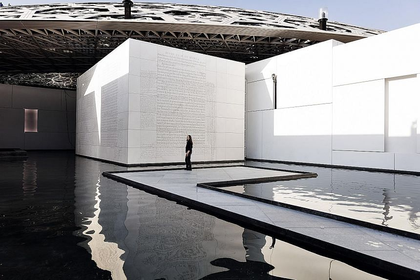 A sculpture (above) by Italian artist Giuseppe Penone at the museum, which has a lace-like ceiling; and American artist Jenny Holzer (left) with her work carved across several walls.