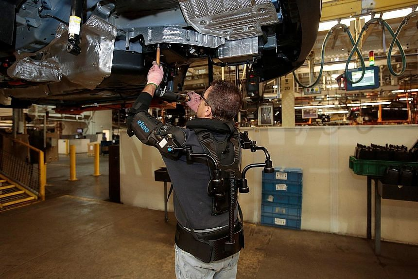 "Ford Motor worker Paul ""Woody"" Collins wears an EksoVest, which takes the stress off his shoulders when performing overhead tasks."
