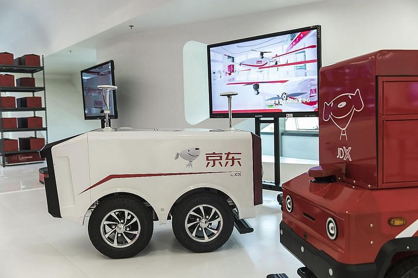 Unmanned delivery vehicles at a showroom inside e-commerce giant JD.com's headquarters in Beijing last month. Online retailers such as JD.com are also investing in drone programmes they hope will one day perform so-called last-mile deliveries, especi