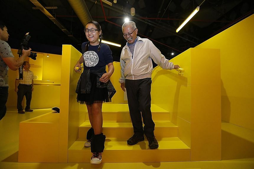 Senior guide Ho Jin Yong, 69, with a guest at the launch of the science centre's latest exhibition, Dialogue With Time - Embrace Ageing, yesterday. She had 4kg weights strapped to her legs, part of a game to simulate the muscle aches that older peopl