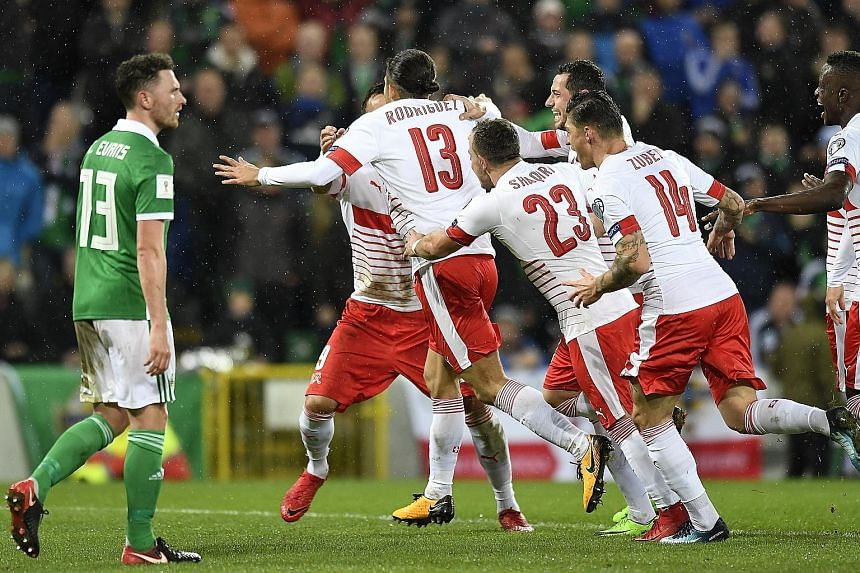 Switzerland players celebrating after Ricardo Rodriguez scored the crucial penalty in the 1-0 win, as Northern Ireland midfielder Corry Evans watches on. The return leg of the World Cup play-off will be played tomorrow.