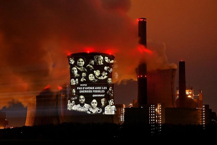 """A light projection that reads """"No future with fossil energies"""" in French on the facade of a coal-fired power plant in Germany. The Paris Agreement calls on the world to cap global warming at """"well below"""" 2 deg C."""