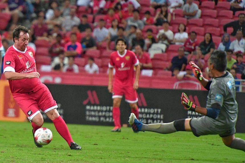 Liverpool masters captain Robbie Fowler attempts to score against Singapore goalie Rezal Hassan.