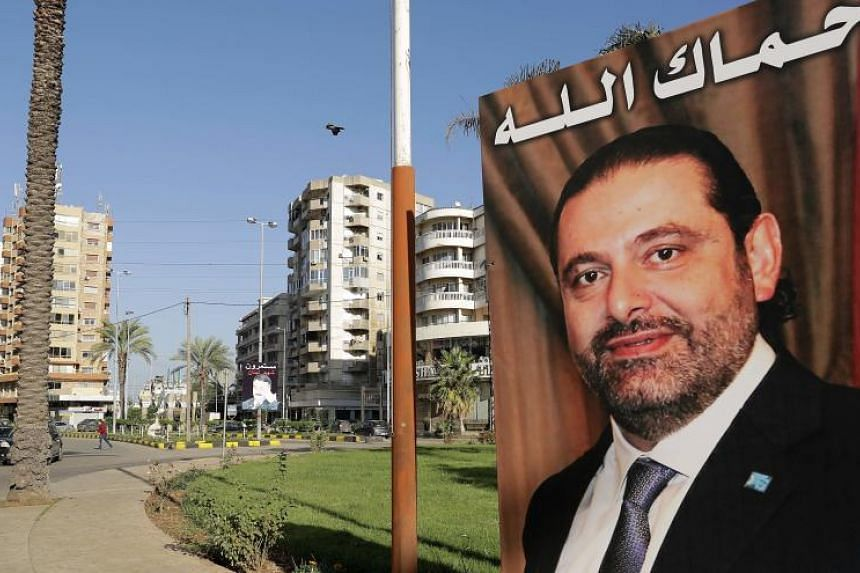 """A poster of Saad Hariri, who resigned last week, hangs in the northern Lebanese port city of Tripoli with an Arabic caption which reads: """"God protect you."""""""
