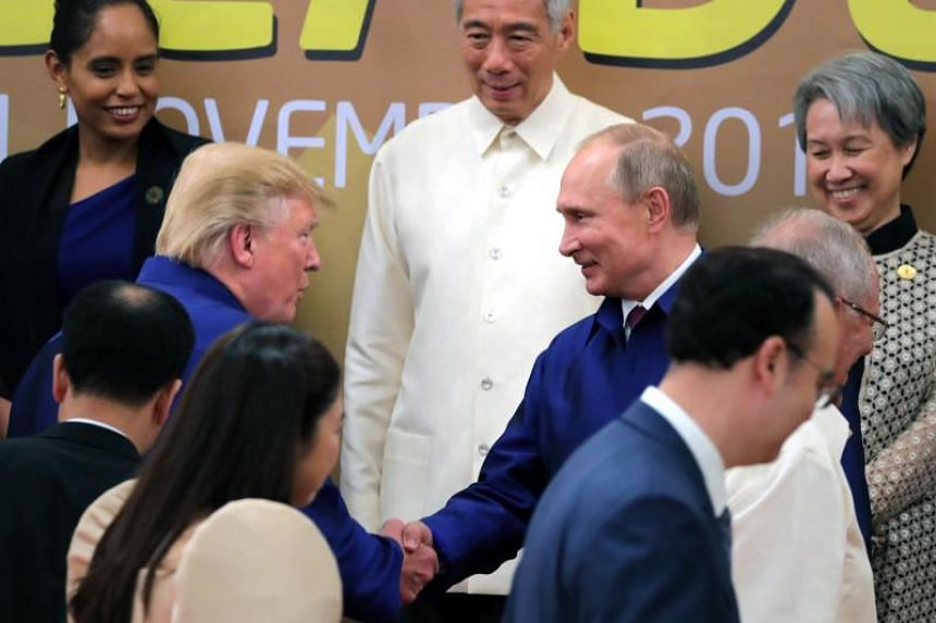 US President Donald Trump shakes hands with Russian President Vladimir Putin as they pose for a group picture during the 25th Asia-Pacific Economic Cooperation (Apec) summit in Da Nang, Vietnam, on Nov 10, 2017.