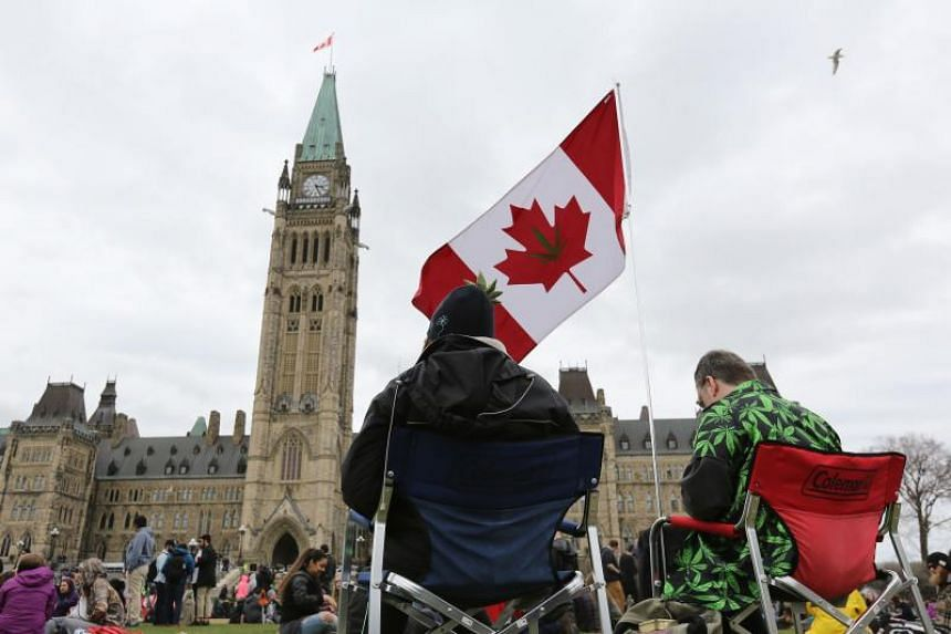 People siting on Parliament Hill waiting for the clock to hit 4.20pm on April 20, 2017 in Ottawa, Ontario.