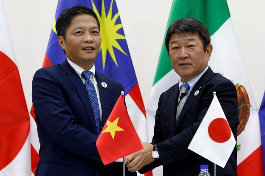 Japan's Minister of Economic Revitalisation Toshimitsu Motegi (R) and Vietnam's Industry and Trade Minister Tran Tuan Anh shaking hands after they attended a news conference on the Trans Pacific Partnership (TPP) Ministerial Meeting during Apec 2017